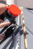 一个屋顶的工作者有安装金属瓦片的电钻的在木房子 库存图片