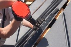 一个屋顶的工作者有安装金属瓦片的电钻的在木房子 免版税图库摄影