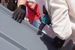 一个屋顶的工作者有安装金属瓦片的电钻的在木房子 免版税库存图片