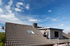 一个屋顶的看法与一个工作的盖屋顶的人的 免版税库存照片
