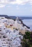 一个山坡的白色传统希腊房子在圣托里尼海岛上  海、船、火山和buil的美丽的景色 免版税库存照片