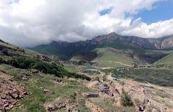 一个山岭地区的照片有小山的、岩石、峭壁和小山、许多绿色植被和岩石 库存图片