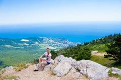 一个山峰的年轻旅客与海和在背景的蓝天,远足 免版税图库摄影