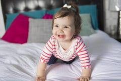 一个岁女孩在床上 免版税库存照片