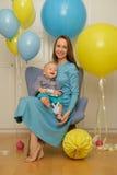 一个岁男婴第一个生日 有坐在椅子的母亲的小孩孩子 库存照片