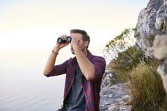 一个岩石山腰的年轻人与双筒望远镜 免版税库存照片