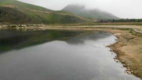 一个岩石海岸山绿松石湖的鸟瞰图在小山中的在多云天气和雾 北部的风景 股票视频