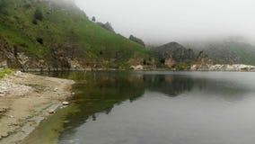 一个岩石海岸山绿松石湖的鸟瞰图在小山中的在多云天气和雾 北部的风景 影视素材