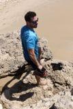 一个岩石的可爱的人在海滩 免版税库存图片