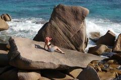 一个岩石的女性反对海 库存图片