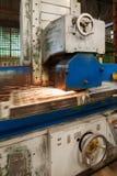 一个工业平磨机器的工作 研一个平的金属零件 免版税库存照片