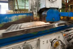 一个工业平磨机器的工作 研一个平的金属零件 免版税库存图片