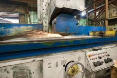 一个工业平磨机器的工作 研一个平的金属零件 库存照片