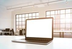 一个工作场所在一个明亮的现代办公室 一张运转的书桌装备有白色拷贝空间的一台现代膝上型计算机在屏幕 Docs s 库存图片