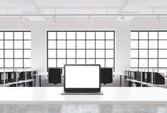 一个工作场所在一个明亮的现代顶楼露天场所办公室 一张运转的书桌装备有白色拷贝空间的一台现代膝上型计算机在Th 库存照片