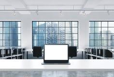 一个工作场所在一个明亮的现代顶楼露天场所办公室 一张运转的书桌装备有白色拷贝空间的一台现代膝上型计算机在Th 免版税库存图片