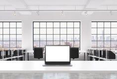 一个工作场所在一个明亮的现代顶楼露天场所办公室 一张运转的书桌装备有白色拷贝空间的一台现代膝上型计算机在Th 图库摄影