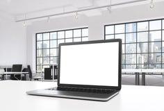 一个工作场所在一个明亮的现代顶楼露天场所办公室 一张运转的书桌装备有白色拷贝空间的一台现代膝上型计算机在Th 免版税库存照片