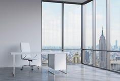 一个工作场所在一个现代壁角全景办公室在纽约,曼哈顿 一把白革椅子和一张白色桌 图库摄影