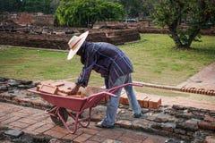 一个工作者人在有独轮车和r的一个建造场所工作 免版税库存照片