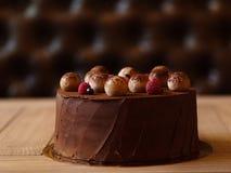 一个巧克力蛋糕的特写镜头用莓和黑醋栗糖果商在被弄脏的背景上把桌放 免版税图库摄影