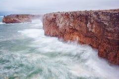 一个巨型岩石的小的渔夫在风暴。 免版税库存图片