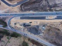 一个巨型的建造场所的空中空气视图有一种重型车辆、推土机和挖掘机的,建立一新的路、工作和unl 免版税库存照片