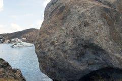 一个巨大的岩石和一艘汽艇在海在拔摩岛,希腊海岛夏时的 库存照片