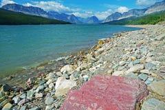 一个巨大的红色自然岩石在海岸线说谎在冰川国家公园 免版税库存照片