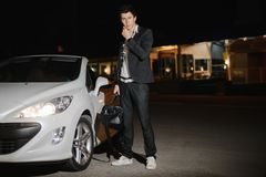 一个帅哥身分的画象在他的白色敞蓬车旁边的 夜生活 在衣服的商人在豪华汽车 库存图片