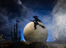 一个帚柄的巫婆以月亮为背景,万圣夜 免版税库存照片