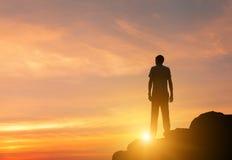 一个常设人的剪影五颜六色的日落的在夏天 免版税库存照片