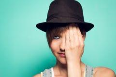 一个帽子和盖的她的眼睛女孩用她的手 库存照片