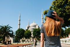 一个帽子的一个女孩旅客从后面在著名清真寺旁边的Sultanahmet广场叫蓝色清真寺  免版税库存照片