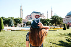 一个帽子的一个女孩旅客从后面在著名Aya索非亚清真寺旁边的Sultanahmet广场在伊斯坦布尔 免版税库存照片