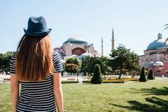 一个帽子的一个女孩旅客从后面在著名Aya索非亚清真寺旁边的Sultanahmet广场在伊斯坦布尔 库存照片