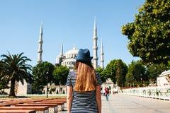 一个帽子的一个女孩旅客从后面在著名清真寺旁边的Sultanahmet广场叫蓝色清真寺  免版税库存图片