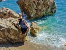 一个帽子的一名妇女在海附近 库存图片