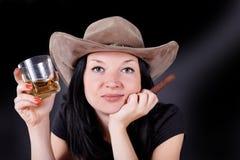 一个帽子的女孩与雪茄和威士忌酒 免版税库存图片