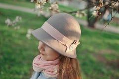 一个帽子的女孩在一个繁茂花园里 免版税库存图片
