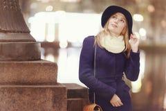 一个帽子的女孩在夜城市 库存图片