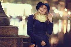 一个帽子的女孩在夜城市 免版税图库摄影
