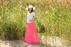一个帽子的女孩在背景夏天风景 免版税库存图片