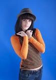 一个帽子的女孩在蓝色背景 免版税图库摄影