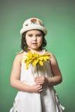 一个帽子的女孩在绿色背景的演播室用向日葵 库存照片