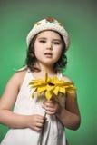 一个帽子的女孩在绿色背景的演播室用向日葵 库存图片