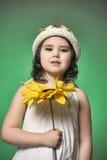 一个帽子的女孩在绿色背景的演播室用向日葵 图库摄影