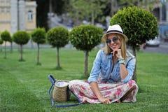 一个帽子的女孩在绿色草坪 图库摄影