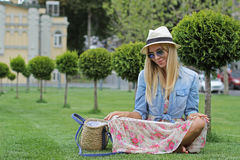 一个帽子的女孩在绿色草坪 库存照片