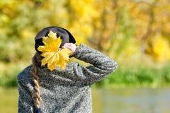 一个帽子的女孩有一束的叶子在河岸站立 回到视图 免版税库存照片